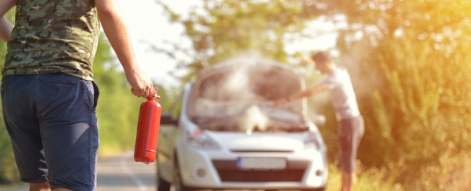 Brave man with fire extinguisher going to a car incident on the road with smoke on the engine