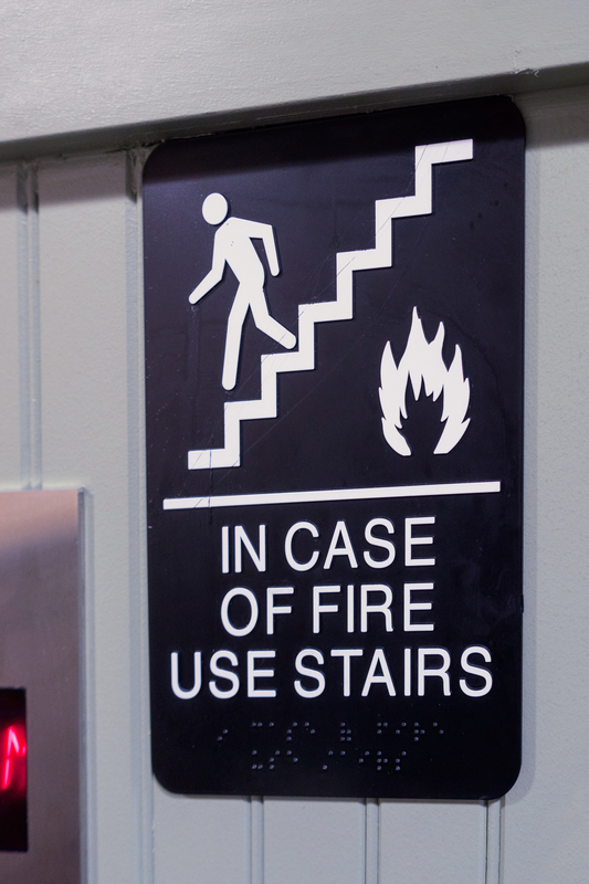 elevator sign in case of fire use stairs with figure, stairs, fire icons