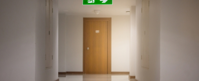 Emergency lighting sign lit above an emergency exit door
